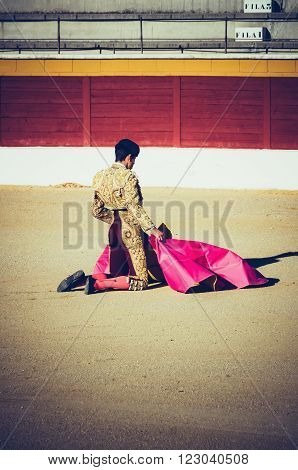An kneeling bullfighter awaiting for the bull in the bullring. Corrida de toros