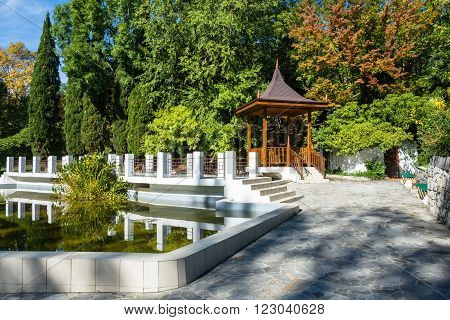 Beautiful gazebo and pond is framed by white stone in the Park-the arboretum of Sochi.