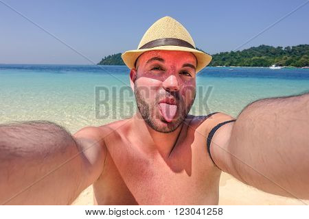 Happy man on vacation making funny face at the beach taking selfie - Handsome guy has fun wearing armpocket - Concept of technology smartphone addiction on single holiday - Soft warm filtered look