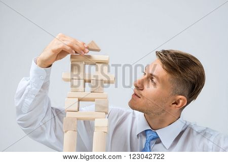 Young handsome businessman building tower of wooden blocks