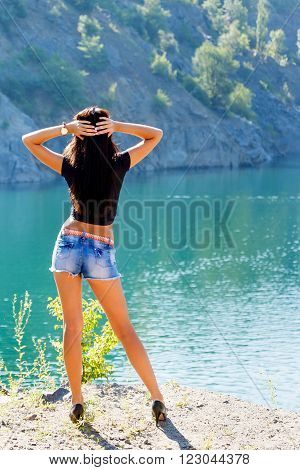Young woman in a black top and denim shorts standing on the shore of a mountain river