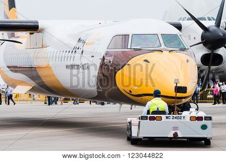 Singapore - February 17 2016: Front of a Bombardier Q400 NextGen in Nok Air livery being pushed into position during Singapore Airshow at Changi Exhibition Centre in Singapore.