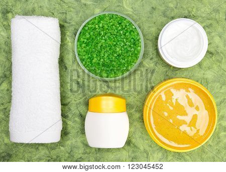 Spa and pampering products. Close-up of white towel, open jars filled with coarse sea salt, natural body scrub and skin care cream on green textured surface. Safe organic cosmetics