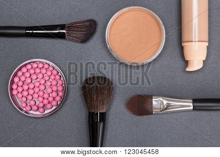 Bottle of liquid foundation, open jars of loose cosmetic powder and blush with makeup brushes on gray textured surface. Basic makeup products to create beautiful complexion