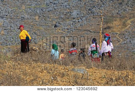 HA GIANG, VIETNAM - FEB 7, 2014: Unidentified Hmong family walking home through a rocky mountain from a weekly traditional flea market.