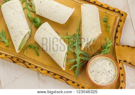 Cold wraps filled with ham and lettuce. Served with yogurt sauce on a wooden cutting board