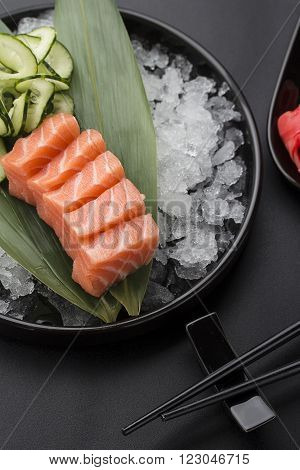 Salmon Sashimi On A Bamboo List And Ice Over Black Background