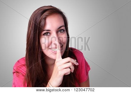 Portrait of a beautiful smiling student show silence gesture. Isolated on gray background caucasian beauty
