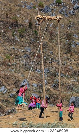 HA GIANG, VIETNAM - FEB 7: Unidentified Hmong children playing with a swing on a holiday called Tet on February 7, 2014.