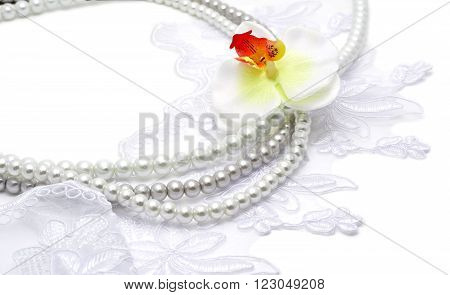 Pearl beads strings on white lace with flowerish tracery