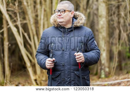 Hiker with walking sticks in winter day