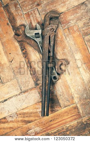 Set of old adjustable spanner pipe wrench and open-end wrench on wooden floor