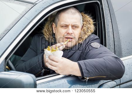 Man eating french fries in the car