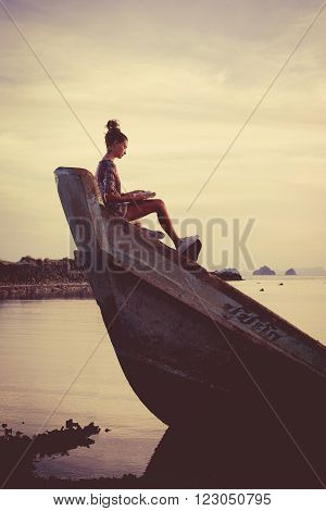 Young woman is sitting on the shipwreck and reading a book. Tropical sunset on the background.