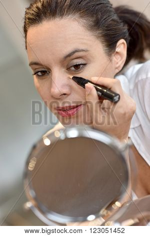 Middle-aged woman applying eye concealer in front of mirror