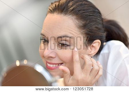 Middle-aged woman looking at mirror