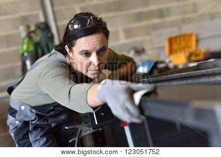 Metalworker sanding down piece of metal