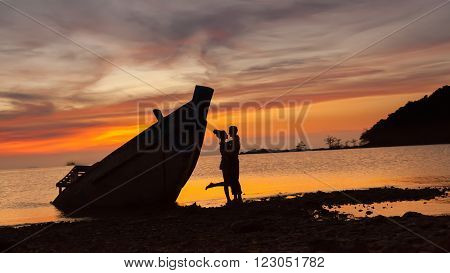 Silhouette Of The Embracing Couple Near The Shipwreck