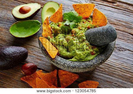 Guacamole with nachos avocado in Mexican molcajete in aged wood table