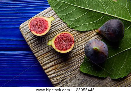 figs raw cut fruits and fig tree leaves on blue wooden table