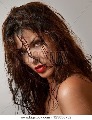Beautiful female portrait with long wet hair, studio shot. Genuine natural redhead looking directly to the camera after a shower. Attractive woman with beautiful eyes on gray background, side view