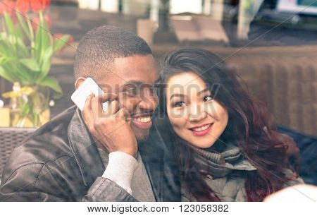 Multiracial couple on date view through cafe window - Afro american man using phone and asian girlfriend facial expression in love - Cheerful mixed race friends - Closeup from glass focus on male