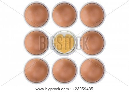 Eggcups full of fresh free range Chicken eggs with one cross section showing boiled heart shaped egg yolk and egg white, isolated on white background