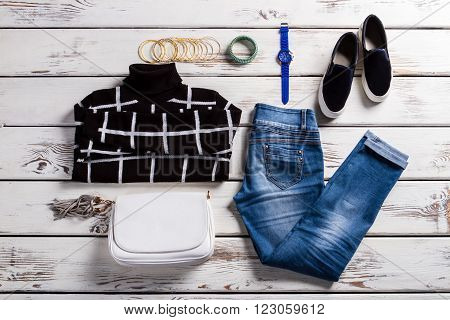 Lady's checkered sweater and jeans. Outfit with pullover on shelf. High collar sweatshirt and accessories. Female casual spring clothing.