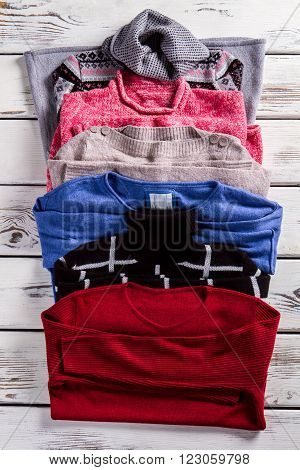 Few sweatshirts and tunic. Warm clothing set on showcase. Choice of pullovers for ladies. Different colored pieces of clothing.