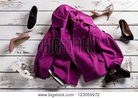 Crumpled purple coat and shoes. Coat with footwear on shelf. Mess in woman's clothing store. Poor quality of clothes delivery.