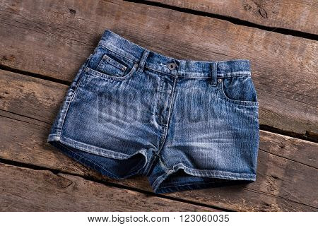 Lady's classic denim shorts. Denim shorts on old floor. Woman's shorts on old shelf. New garment from retro boutique.