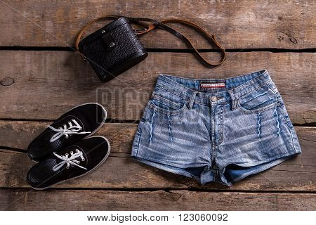 Woman's denim shorts with handbag. Retro clothing on wooden table. Summer sale at vintage boutique. Lady's classic clothes for summer.