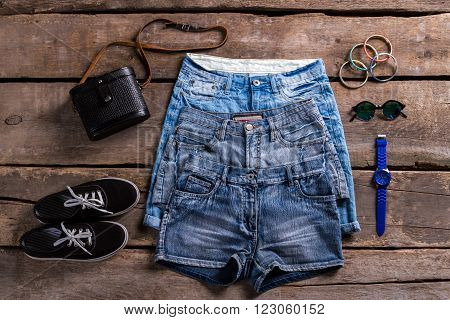 Lady's denim shorts and accessories. Woman's clothing on old floor. Small accessories with denim garments. Simple classic clothes and bracelets.