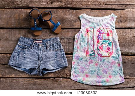 Woman's floral top and shorts. Girl's outfit on old showcase. Aged shelf with girl's clothes. New outfit on aged table.