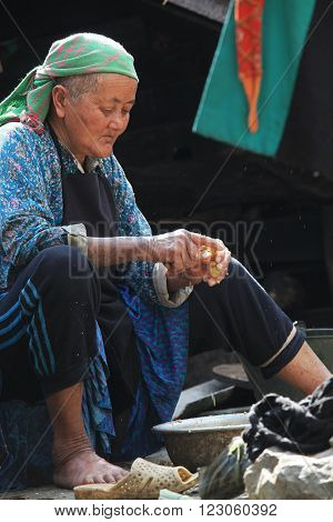 HA GIANG, VIETNAM - FEB 7, 2014: Unidentified old minority Hmong woman scraping ginger under the sunlight.