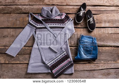 Tunic with jeans and keds. Spring outfit on old table. Lady's clothing on attic floor. Female clothes on wooden planks.