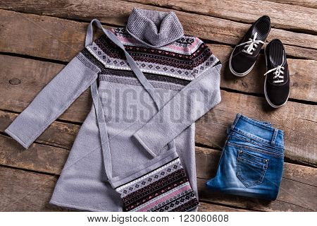 Gray tunic with blue jeans. Clothing on old wooden planks. Female outfit lying on floor. Spring clothes on brown table.