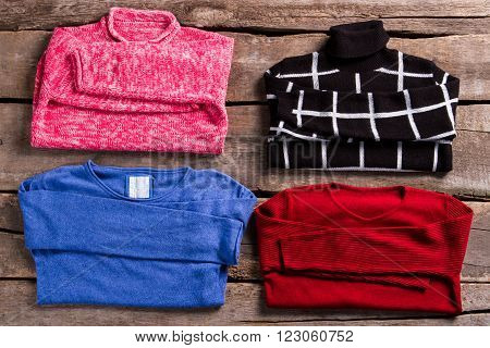 Female sweatshirts of different colors. Sweaters on old wooden table. Colorful pullovers on wooden planks. Different sweatshirts at vintage store.
