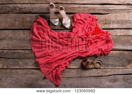 Dress with shoes and bracelets. Lady's outfit on brown table. Aged shelf with stylish outfit. Clothing on aged wooden background.