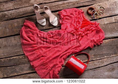 Red dress with bright accessories. Female outfit on brown table. Old table with fashionable clothes. Vintage fashion store showcase.