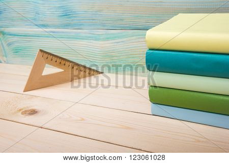 Back to school. Stack of colorful books on wooden table. Composition with vintage old hardback books, diary on wooden deck table. Books stacking. Copy Space. Education background.
