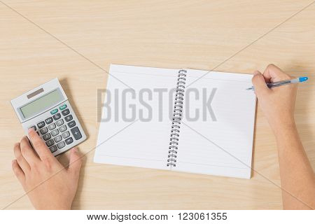 hand press calculator and writting on notebook with pen