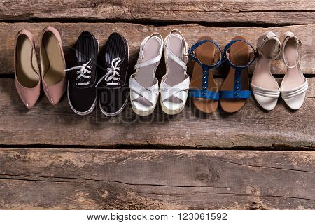 Pairs of woman's stylish footwear. Shoes on old wooden shelf. Shoe row at vintage store. Retro boutique footwear sale.