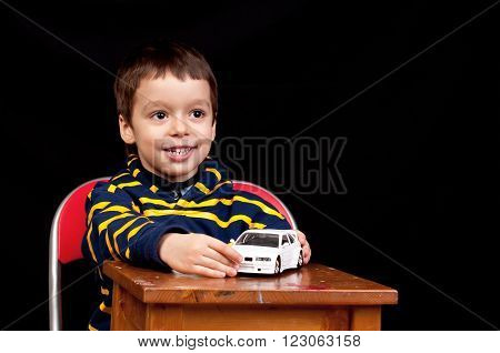 Smiling Little Boy Plays Indoor With Toy Car