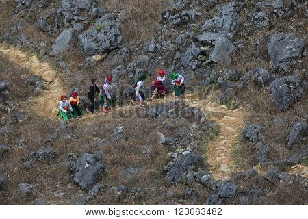 HA GIANG, VIETNAM - FEB 7, 2014: A group of unidentified Hmong residents walking on a small path on the side of a mountain in Dong Van rocky plateau.