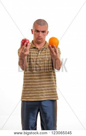 Puzzled Young Man Confused, He Doesn't Know What To Choice Between An Apple An An Orange