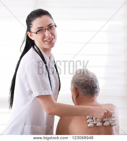 Nurse Masagging Old Man With Roller Massager