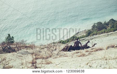 Young man sitting on snag on coast and enjoying view of sea rear view