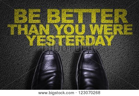 Top View of Business Shoes on the floor with the text: Be Better Than You Were Yesterday