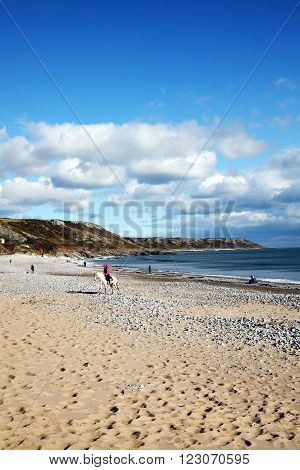 Port Eynon Bay, West Glamorgan,Wales, UK, March 5, 2016 : Holidaymakers on vacation making the most of the sun on a golden sandy beach of the Gower Peninsular